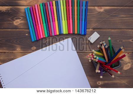 Pencils markers and the album on a dark wooden table top view