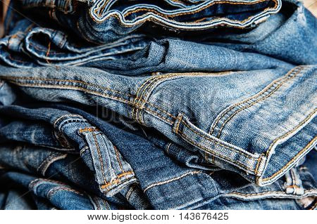 stack of blue jeans closeup, fashion background
