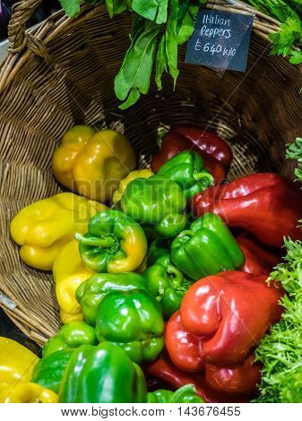 Green, red and yellow peppers in basket on sale at a Borough farmers market in London, England, UK