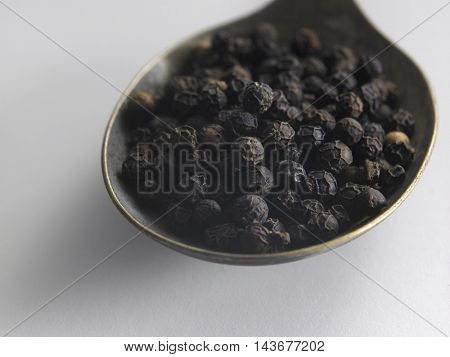 close up spoon of black peppercorn on the white background