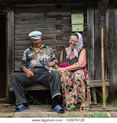 beautiful mature russian couple have fun outside of their house in village. The woman clothed in a scarf keeps the broom. They stroking domestic cat