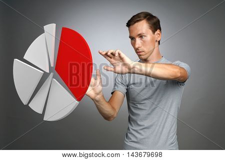 Man in t-shirt working with pie chart on grey background.