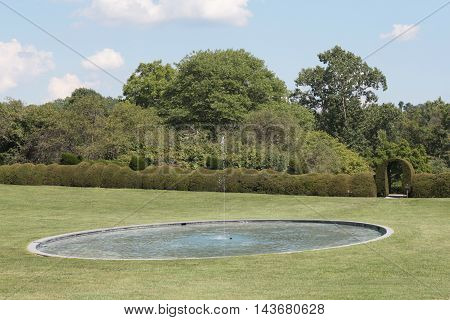 A large round pool of water with a fountain.