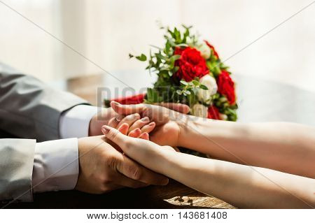 groom holding bride's hands with beautiful wedding bouquet at table.