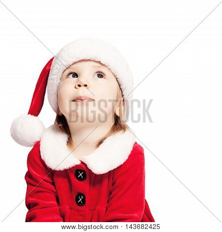Christmas Baby in Santa Hat Looking Up. Child Isolated on White