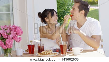 Couple feeding each other at breakfast