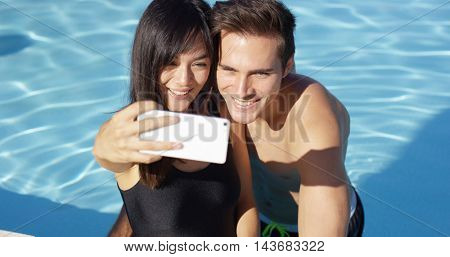 Handsome couple take photo while standing in pool