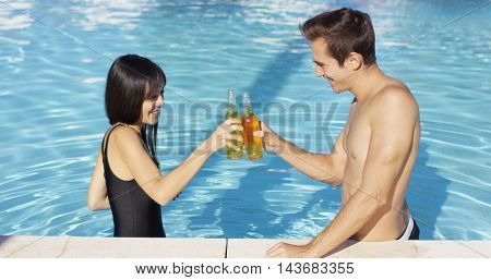 Handsome young couple toasts in swimming pool