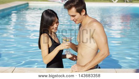 Cute mixed couple holding martini glasses in pool