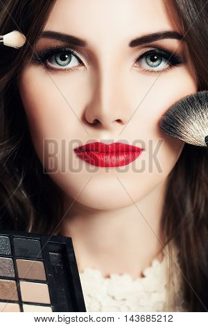 Makeup Beauty concept. Beautiful Woman with Make-up Brushes and Eye Shadow palettes