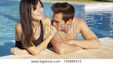 Man in pool standing with girlfriend kisses her