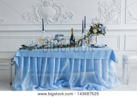 Wedding decorations with candles, cake and bottle with wine and beautiful flowers. serenity color