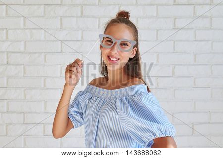 Attractive girl in summer clothes is posing with paper glasses standing against white background