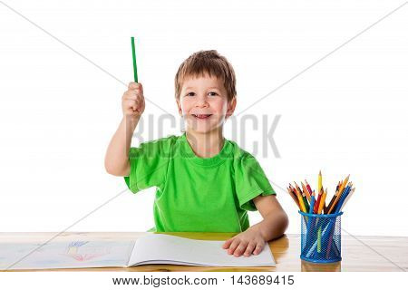 Creative smiling little boy at the table with pencils, pointing up, gesturing idea, isolated on white