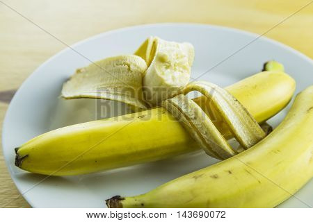 Bananas in plate on yellow wooden background