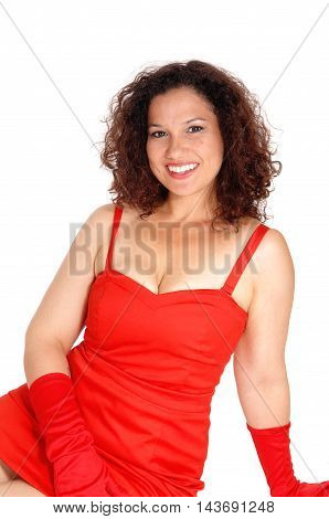 A beautiful young woman in a red dress and cloves sitting on the floor smiling isolated for white background.