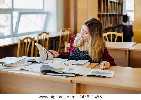 Concentrated attractive female student sitting at desk in old university library preparing for exam and reading books. Education process.