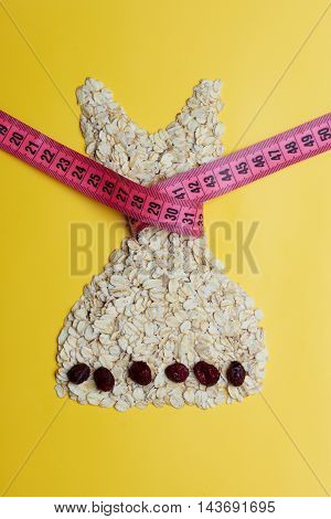 Dieting healthy eating slim down concept. Female dress shape made from oatmeal dried fruit with measuring tape around thin waist on yellow