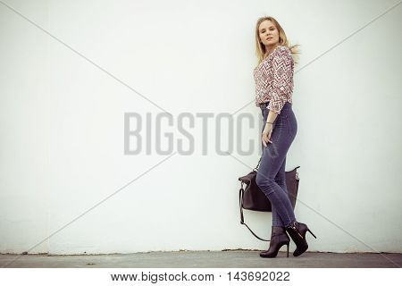 Urban style. Stylish fashionable beauty woman with black bag handbag. Blondie girl model posing outside. Fashion of female idea.