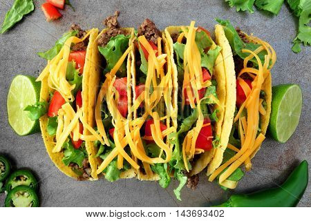 Traditional Hard Shelled Tacos With Ground Beef, Lettuce, Tomatoes And Cheese, Overhead View On Rust