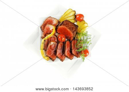 grilled meat chunk and slices on white plates