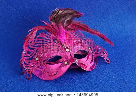 A carnival mask displayed on a blue background