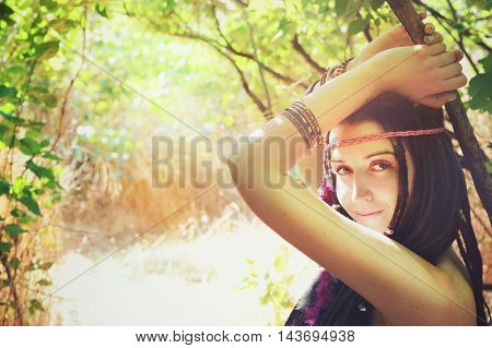 Young hippie girl with feathers in her hair and headband posing outdoor in sunny park, looking at camera and smiling, natural lifestyle concept, space for text