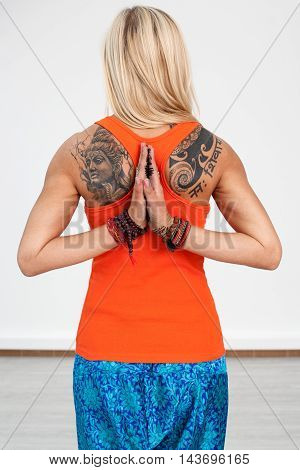 Blonde woman with tattoos and palms joined behind the back
