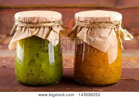 Pumpkin-Orange-Ginger-Poppy seed and Kiwi-Mint homemade jam on wooden background.