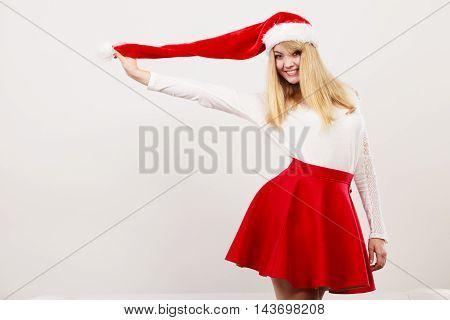 Happy smiling cute woman in santa helper hat. Pretty blonde girl in studio on gray. Christmas xmas season.