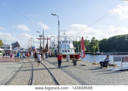 KOLOBRZEG - AUGUST 15: Tourists enjoy the sunny weather and walking on the harbor on 15 August 2016 in Kolobrzeg, Poland.