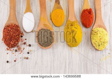 Various Spices In Wooden Spoons On Wooden Table