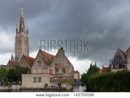 Brugge Belgium - August 10 2016: The spire of the Notre Dame Cathedral towers over the Old Sint Jans Hospital. Sky filled with dark rain clouds. Canal in foreground.