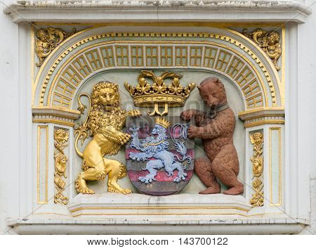 Brugge Belgium - August 10 2016: Portrait of the Bruges Coat of Arms in three dimensional mural on facade of medieval Palace of Justice. Gold Brown Blue and more.