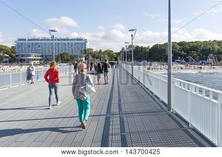 KOLOBRZEG - AUGUST 15: Tourists enjoy the sunny weather and walk along the pier on 15 August 2016 in Kolobrzeg, Poland.