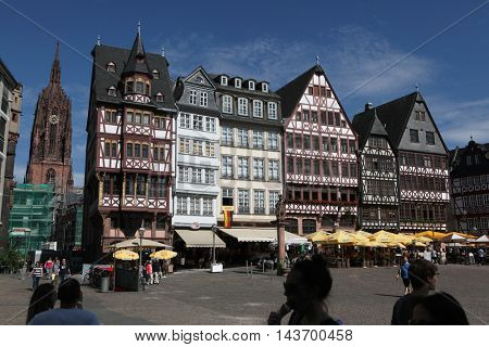 FRANKFURT AM MAIN, GERMANY - JUNE 14, 2015: Tourists in front of the reconstructed half-timbered houses at the Romerberg in Frankfurt am Main, Germany. Frankfurt Cathedral is seen in the background.