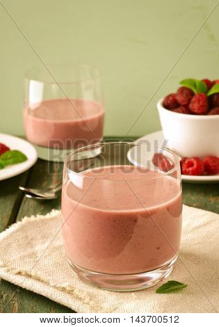 Healthy berry with raspberry, oatmeal and mint in a glass, on wooden table, toned