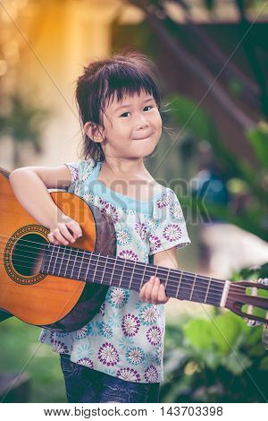 Happy asian girl smiling and playing classic guitar with bright sunlight at home. Positive human emotion. Playful asian child outdoor in nature on sunny day. Vintage tone effect.