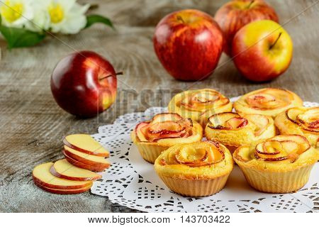 Apple shaped roses muffins on wooden background. Sweet apple dessert pie. Homemade apple rose pastry.