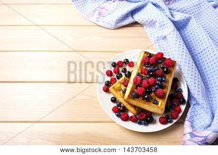 Soft Belgian waffles with blueberry raspberry and blackcurrant copy space. Breakfast waffles with fresh berries.