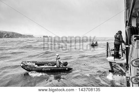 SOUTH GEORGIA, GREAT BRITAIN - NOV 9, 2012: Unidentified man goes down to get a place in a boat in the Atlantic Ocean. Atlantic Ocean is the world's second largest ocean