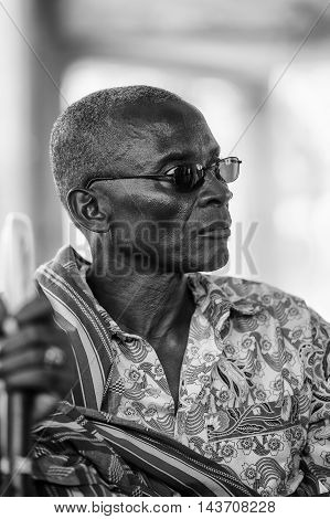 KARA, TOGO - MAR 9, 2013: Unidentified Togolese man in glasses in the traditional clothes. People in Togo suffer of poverty due to the unstable econimic situation