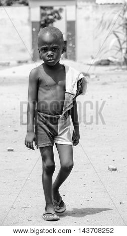 KARA, TOGO - MAR 9, 2013: Unidentified Togolese boy with sad eyes walks in the street. Children in Togo suffer of poverty due to the unstable econimic situation