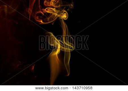 Abstract art. Color yellow red smoke from the aromatic sticks on a black background. Background for Halloween. Texture fog. Design element. The concept of aromatherapy.