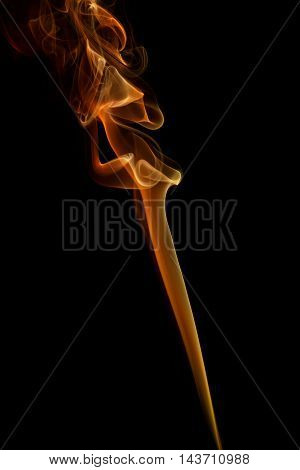 Abstract art. Color yellow orange smoke from the aromatic sticks on a black background. Background for Halloween. Texture fog. Design element. The concept of aromatherapy.