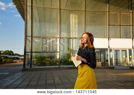 Girl holds in the hands of a clutch. Business style clothing. Next to the office center. Girl waiting for a meeting.