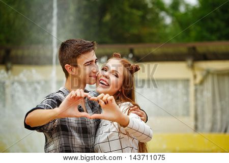 Enamoured teenagers huddled together. Girlfriend and boyfriend strolling in a city park. The boy and the girl made a heart symbol from hands. First love. He falls in love. Date.