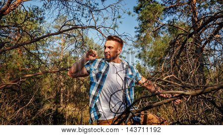 Lumberjack holding an ax. Woodcutter in a plaid shirt. Felling trees. Logging. Manual labor.