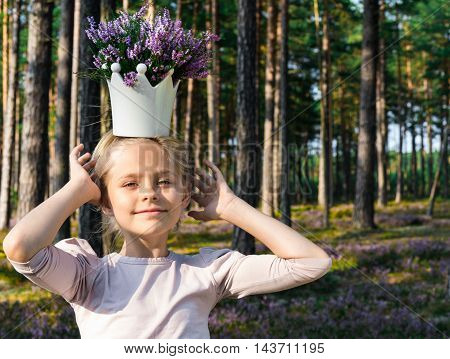 Beautiful child holding a crown on his head with heather. Summer.