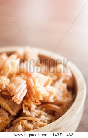 Fried shrimp chins snack in wooden bowl, stock photo